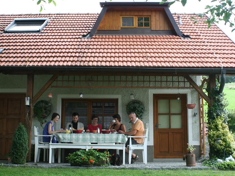 """Außenansicht vom Haus \""""Am Römerradweg\"""", Familie frühstückt auf der Terasse"""