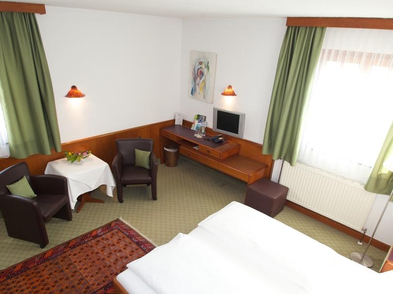 Zimmer im Hotel Gasthof Zillner's Einkehr mit Doppelbett, TV und Sitzgelegenheit