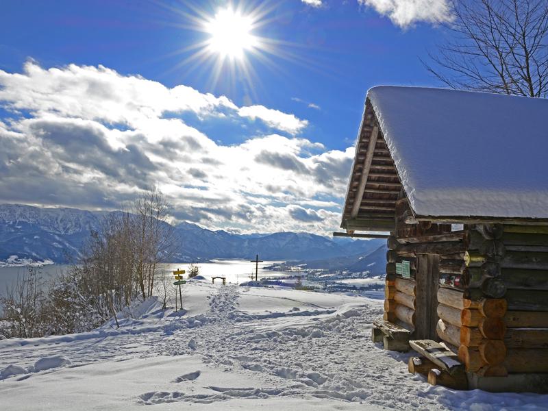 Blockhütte mit Schneedache inmitten einer Winterlandschaft am Buchberg mit Blick zum Attersee, Salzkammergut.