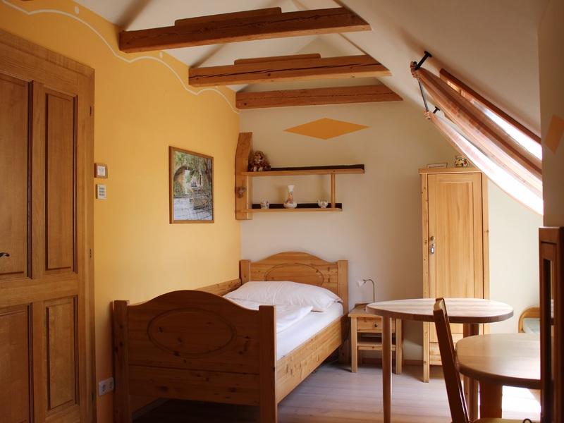 """Zimmer im Haus \""""am Römerradweg\"""" mit Einzelbett und Sitzgelegenheit"""