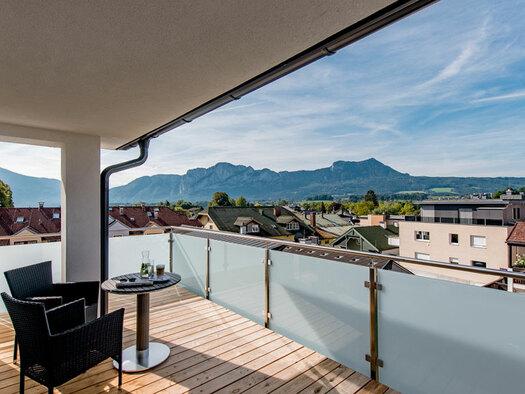 Terrasse mit 2 Sesseln Tisch mit Getränke drauf, Blick über die Dächer zur Drachenwand. (© Hotel Krone)