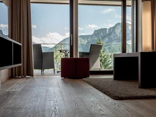 Blick vom Wohnbereich mit Sideboard, Fernseher, Hocker, Tisch auf die Terrasse mit Tisch und Stühle, Aussicht auf die Berge. (© Lackner)