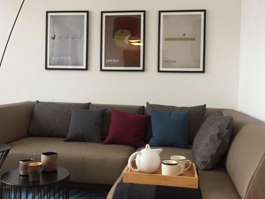 Wohnbereich mit Couch, kleinem Tisch, Tablett mit Kanne und Tassen und Bildern an der Wand. (© Reisch-Raich)
