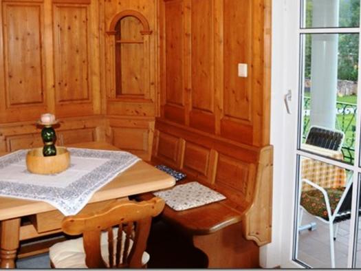Eßbereich mit Eckbank Tisch und Stühle, seitlich Balkontür mit Blick auf die Terrasse wo sich ein Tisch und Stühle befinden. (© Pöllmann)