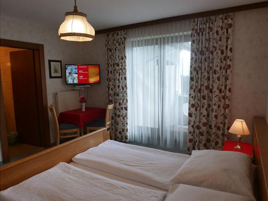 Schlafzimmer mit Doppelbett, Nachtkästchen mit Tischlampe, im Hintergrund eine Balkontüre, Tisch mit Stühlen, darüber ein Fernseher, offene Tür ins Badezimmer. (© Ramsauer)