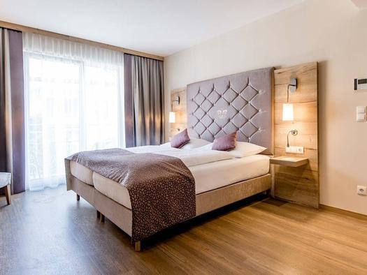 Doppelbett, seitlich eine große Balkontür. (© Hotel Krone)