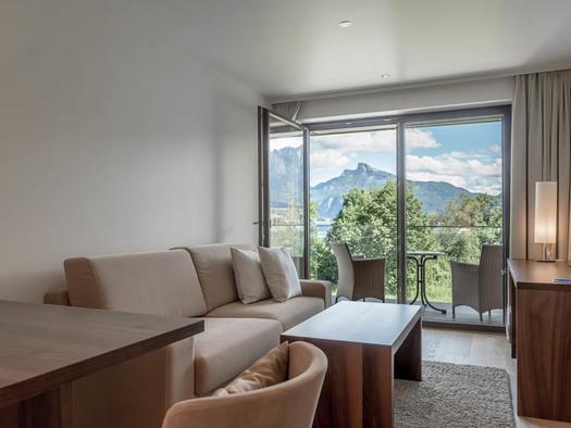 Tisch mit Stuhl, Couch, Tisch, seitlich eine Kommode/Tisch mit Lampe und Fernseher, im Hintergrund Blick durch die offene Balkontür auf die Terrasse mit Tisch und Stühle, Blick auf die Landschaft, See und Berge. (© Lackner)