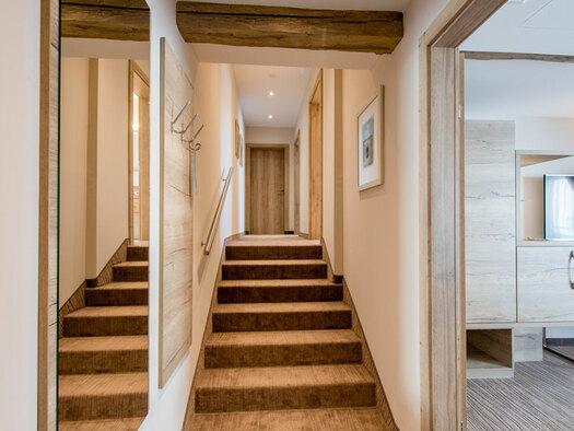 Treppen, davor großer Spiegel an der Wand, Einblick in eines der Zimmer, Sideboard mit Schreibtisch, kleiner Stuhl, darüber TV. (© Hotel Krone)