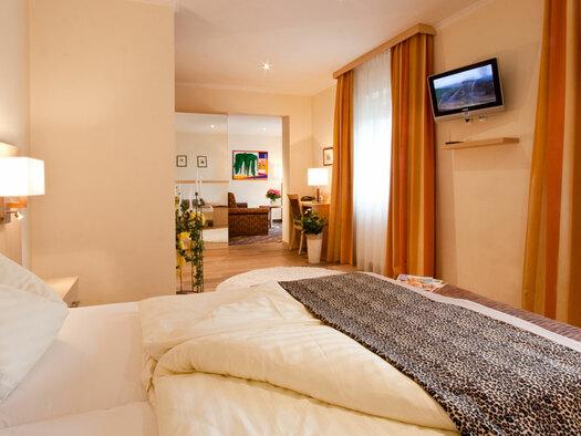 Doppelbett mit Leselampe an der Seite, TV an der Wand, etwas weiter weg kleiner Schreibrtisch mit Stuhl und Sofa. (© Hotel Krone)