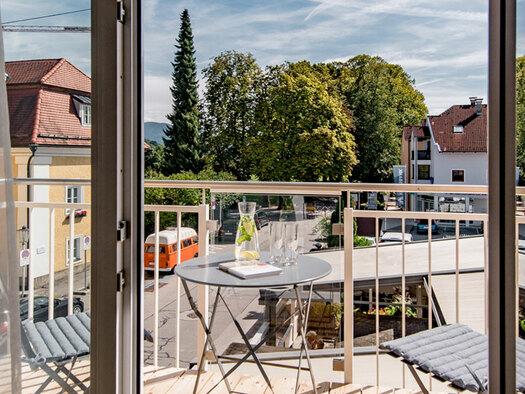 Balkon, Aussicht auf Bäume und Häuser, Tisch mit Getränken und 2 Sesseln. (© Hotel Krone)