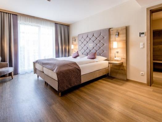 Blick auf das Bett, Sessel, im Hintergrund eine große Balkontür. (© Hotel Krone)