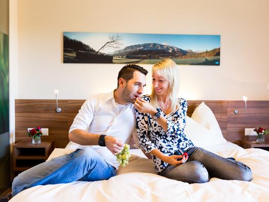 Personen sitzen auf einem Bett und essen Weintrauben, im Hintergrund ein Bild. (© Ellmauer)