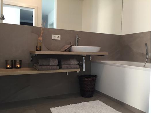 Badezimmer mit Waschbecken, Spiegel und Badewanne. (© Reisch-Raich)