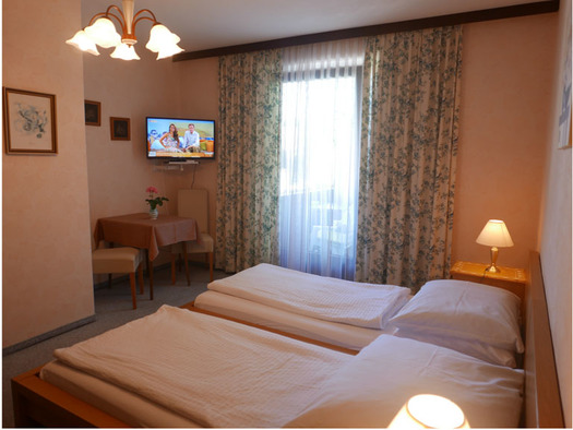 Schlafzimmer mit Doppelbett, Nachtkästchen mit Tischlampe, im Hintergrund Tisch mit Stühlen, im Eck ein Fernseher an der Wand, Balkontür. (© Ramsauer)