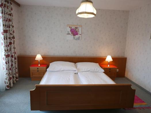 Schlafzimmer mit Doppelbett, Nachtkästchen, Tischlampen, im Hintergrund ein Bild. (© Ramsauer)