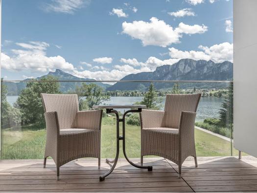 Terrasse mit Tisch und Stühle, Blick auf die Landschaft, den See und die Berge. (© Lackner)