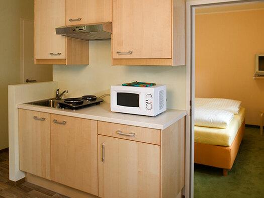 Küchenzeile mit Mikrowelle und Herdplatten. (© Oberschmid)