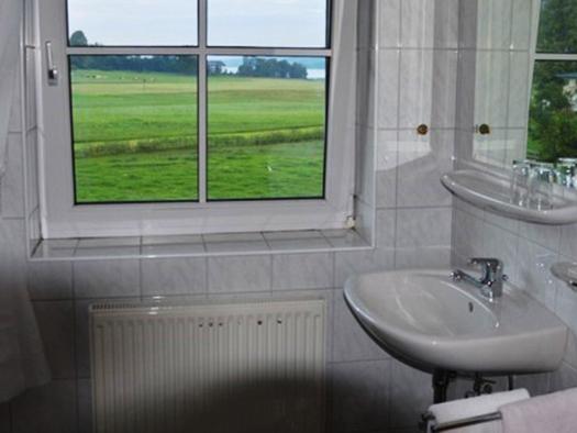 Badezimmer mit Waschbecken, Spiegel, Ablage mit Gläser, Föhn, im Hintergrund ein Fenster mit Blick auf die Landschaft und den See. (© Pöllmann)