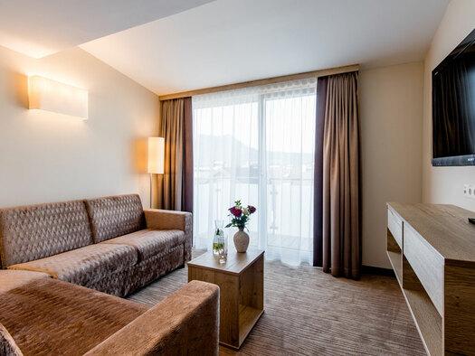 Couch mit kleinem Tisch, Blumenvase, Sideboard, TV an der Wand. (© Hotel Krone)