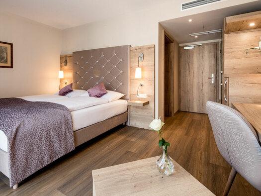 Doppelbett mit Nachtkästchen und Lampe, Schreibtisch mit Stuhl und Lampe, Bild an der Wand. (© KarinLohbergerPhotography)