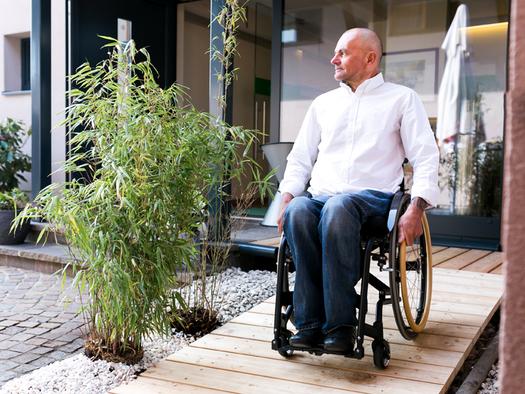 Person fährt im Rollstuhl in den Garten. (© Ellmauer)