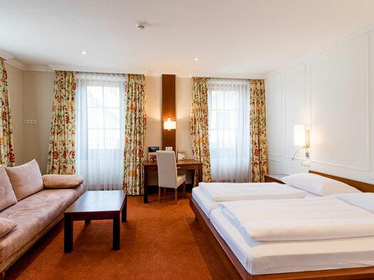 Doppelbett mit Nachtkästchen und Lampe, Couch und kleinem Tisch, lange Vorhänge, kleiner Schreibtisch mit Sessel. (© Hotel Krone)