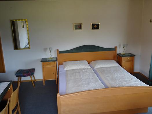 Schlafzimmer mit Doppelbett, Nachtkästchen mit Tischlampen, Hocker und Spiegel. (© Tourismusverband MondSeeLand)