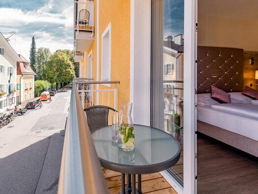 Tisch mit Sessel und Getränke am Balkon, Doppelbett mit Zierkissen und Lampe an der Seite. (© Hotel Krone)
