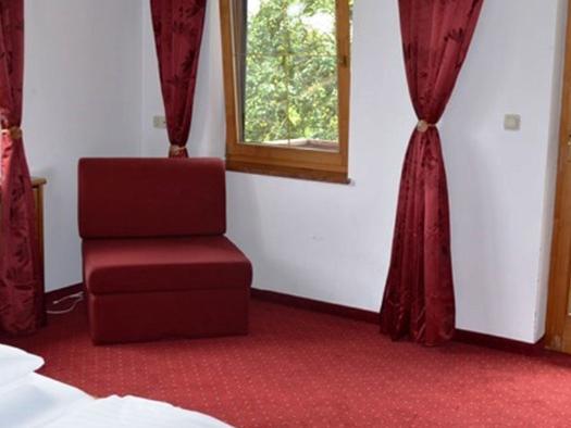 Schlafzimmer im Hintergrund ein gemütlicher Sessel und Fenster. (© Pöllmann)