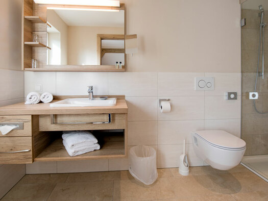 Waschtisch aus Holz mit Handtüchern, Spiegel mit Ablagemöglichkeit, WC und Dusche. (© Hotel Krone)