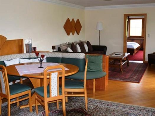 Wohnbereich, mit Eckbank, Tisch und Stühle, dahinter eine Couch, im Hintergrund eine offene Tür mit Blick ins Schlafzimmer. (© Pöllmann)