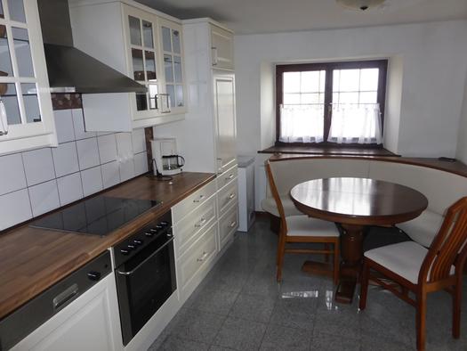 Küche mit Herd, Eckbank, Tisch und Stühle, im Hintergrund ein Fenster. (© Taubenberger)