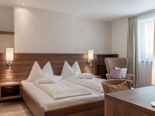 Doppelbett, Nachtkästchen, Lampen, gemütlicher hoher Sessel, seitlich ein Fenster. (© Lackner)