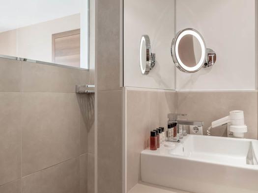 Badezimmer mit Waschbecken, Fön, Kosmetikspiegel, Pflegeprodukte in kleine Flaschen. (© Lackner)