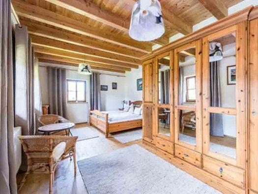 Schlafzimmer mit Doppelbett, im Vordergrund seitlich ein Kasten, Tisch und Stühle. (© Gaderer)