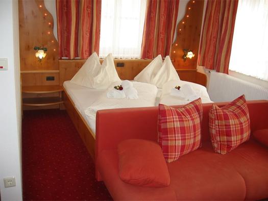 Schlafzimmer mit Doppelbett , im Vordergrund Couch mit Polster. (© Stabauer)
