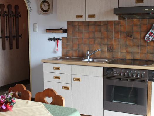Blick auf die Küche mit Herd und Geschirrspüler, im Vordergrund ein Tisch mit Stuhl. (© Fam. Winklhofer)