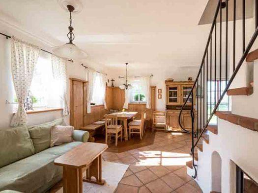Wohnbereich mit Couch, Tisch, im Hintergrund ein Esstisch mit Stühlen, seitlich die Stiege mit einem Geländer. (© Gaderer)