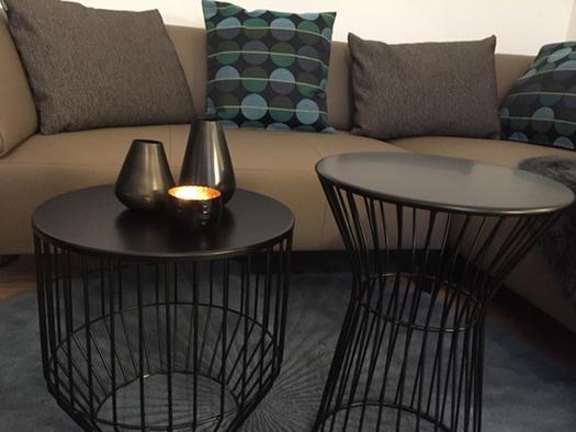 Wohnbereich mit Couch und kleinen Tischen mit Kerzen. (© Reisch-Raich)