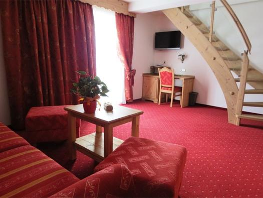 Wohnbereich mit Couch, Tisch und Hocker, Balkontür, Tisch und Stuhl, darüber ein Fernseher, Holzstiege. (© Stabauer)