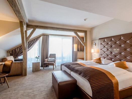 Doppelbett mit Kissen, Schreibtisch mit Stuhl und Lampe, Sessel mit Zierkissen, Beistelltisch. (© Hotel Krone)