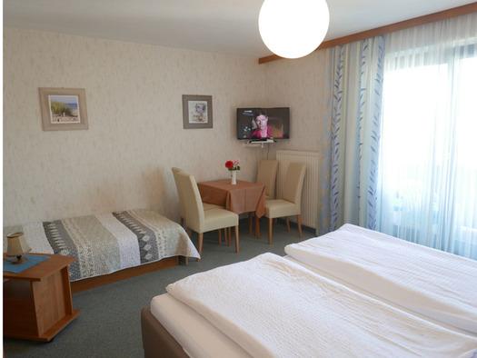 Schlafzimmer mit Doppelbett, seitlich eine Balkontür, im Hintergrund ein Einzelbett, Tisch und Stühle, Fernseher an der Wand. (© Ramsauer)