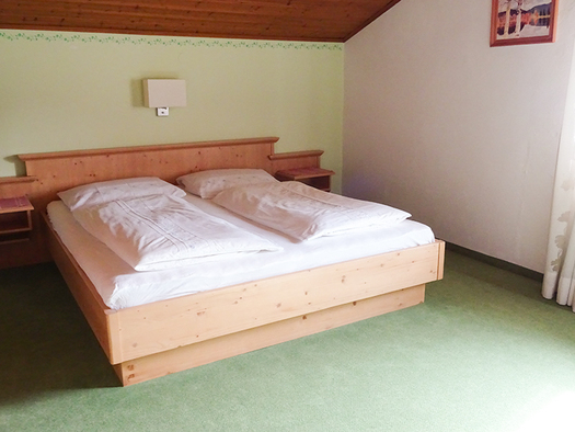 Doppelbett, seitlich ein Fenster. (© Gästehaus Pichler)