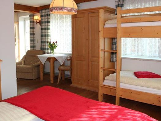 Schlafzimmer, im Vordergrund ein kleiner Teil vom Doppelbett, im Hintergrund ein Stockbett, seitlich steht ein Tisch mit Stühle. (© Mairhofer)