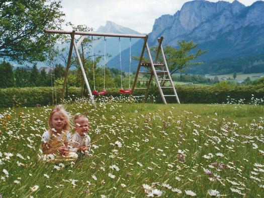 Kinder sitzen in der Blühenden Wiese, im Hintergrund eine Schaukel und die Berge. (© Pichler)