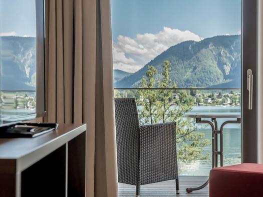 Blick durch die Balkontür auf die Terrasse mit Stuhl und Tisch, Aussicht auf den See und die Berge. (© Lackner)
