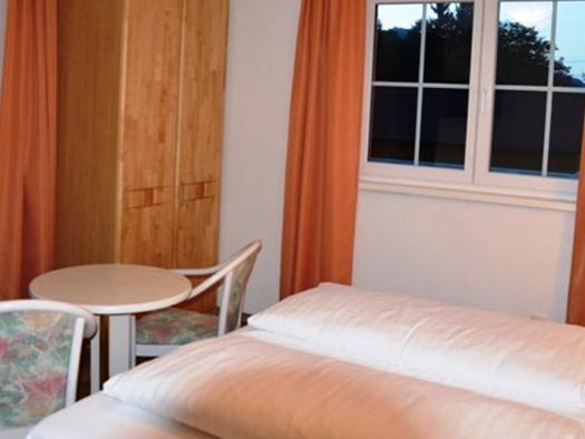 Schlafzimmer mit Doppelbett, davor Tisch und Stühle, im Hintergrund Kasten und Fenster. (© Pöllmann)
