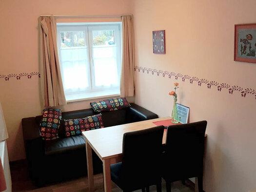 Couch mit Zierkissen, Tisch mit 2 Stühlen, Blume am Tisch. (© Oberschmid)