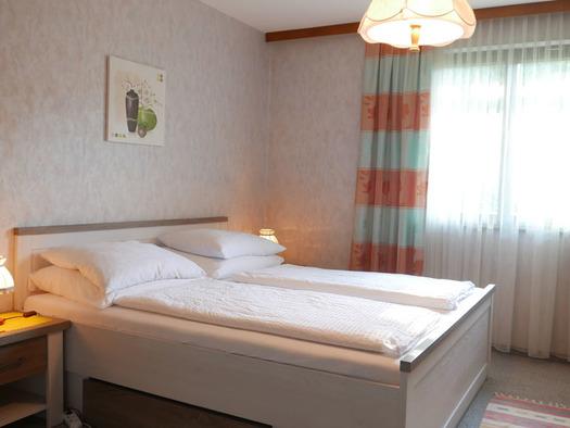 Schlafzimmer mit Doppelbett, Nachtkästchen mit Tischlampen, im Hintergrund ein Fenster. (© Ramsauer)