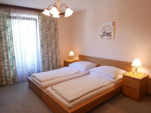 Schlafzimmer mit Doppelbett, Nachtkästchen, Tischlampe, seitlich im Hintergrund eine Balkontür. (© Ramsauer)